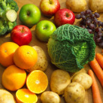 SELECTION OF FRESH FRUIT AND VEGETABLES WITH APPLES ORANGES GRAPES POTATOES CARROTS BROCOLLI AND CABBAGE